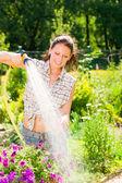 Summer garden smiling woman watering hose flower — Stock Photo