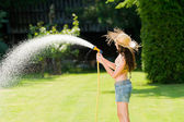 Summer garden woman play with water hose — Stock Photo