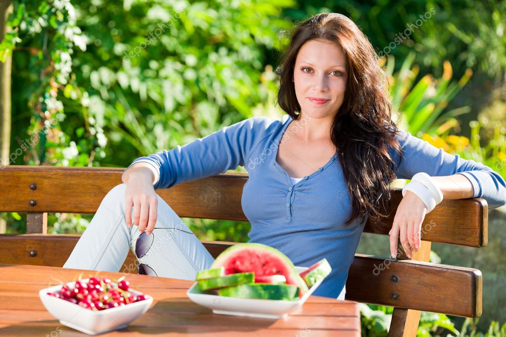 Beautiful young woman fresh summer fruit sitting on garden terrace — Stock Photo #6441232