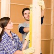 Home improvement smiling couple with spirit level — Stock Photo