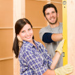 Home improvement smiling couple with spirit level - Stock Photo