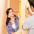 Home improvement smiling couple with spirit level — Stock Photo #6696155