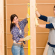 Home improvement smiling couple with spirit level — Stock Photo #6696157