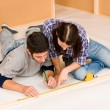 Home improvement young couple measure with rule - Stock Photo