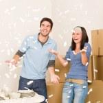 Move home cheerful couple throw Styrofoam peanuts — Stock Photo