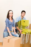 Moving new home young couple carry chairs — Stock Photo