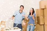 Verplaatsen huis vrolijke paar gooien styrofoam pinda 's — Stockfoto