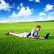 Young man use a notebook on green field — Stock Photo #5981195