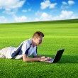 Young man use a notebook on green field — Foto de Stock