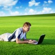 Young man use a notebook on green field — Stok fotoğraf
