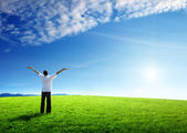 Happy young man on green field — Stock Photo