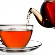 Tea being poured into glass tea cup isolated on a white backgrou — Stock Photo