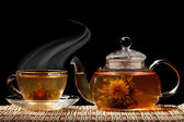 Glass teapot and a cup of green tea on a black background — Stock Photo