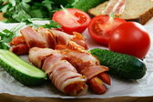 Sausages wrapped in bacon with vegetables and herbs. — Stock Photo