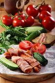Salchichas envuelven en tocino con verduras y hierbas. — Foto de Stock
