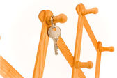 House key hanging on wooden hook — Stock Photo