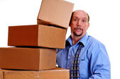 Man carrying heavy boxes with one about to fall. — Stock Photo