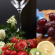 Wine and different fruits on dark background — Stock Photo