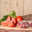 Meat and cut vegetables on table — ストック写真