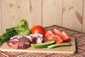 Meat and cut vegetables on table — Stock Photo
