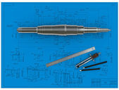 Metal shaft, compasses, rulers and pencils at an engineering drawing — Stock Photo
