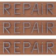 "On a wooden board with nails chrome engraved the word ""REPAIR"" - Stock Photo"