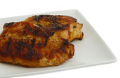 Grilled chops on square plate — Stock Photo