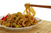Pad Thai dish on straw pad with chopsticks — Stock Photo