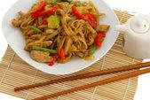 Pad Thai dish on straw pad with chopsticks — Stock Photo