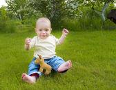 Malé dítě sedět na trávě — Stock fotografie