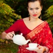 Woman in Indian sari with teapot and cup of tea — Stock Photo