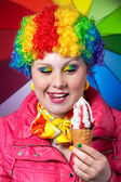 Clown with rainbow make up eating ice cream — Stock Photo