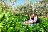 Couple sitting under bloomy tree — Stock Photo