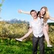 Couple having fun around bloomy trees — Stock Photo #6088084