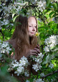 Woman smelling flower in the garden — Stock Photo