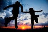 Silhueta de casal correndo para o pôr do sol — Fotografia Stock