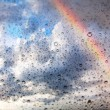 Rainbow and water drops on glass texture — Stock Photo