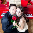 Couple with rose near red piano — Stock Photo