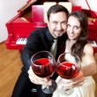 Stock Photo: Couple with glasses of wine near piano