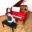 Woman playing the red grand piano - Stock Photo