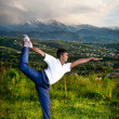 Yoga natarajasana dancer pose in mountains — Stock Photo