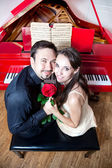 Couple avec rose près de piano rouge — Photo
