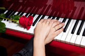 Hands of married couple on piano — Stock Photo