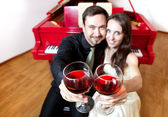 Couple with glasses of wine near piano — Stock Photo