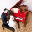 Couple playing the red piano - Stock Photo