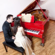 Couple playing the red piano — Stock Photo #6632971