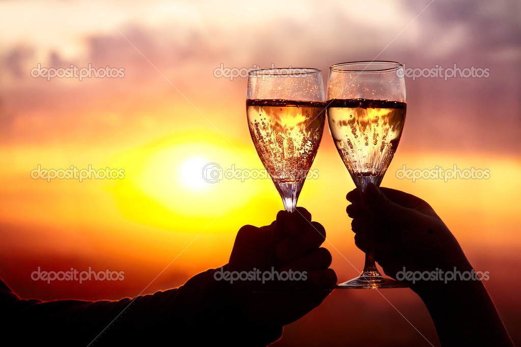Man and woman clanging wine glasses with champagne at sunset dramatic sky background — Stock Photo #6633032