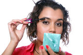 Beauty girl looks in mirror and paints eyelashes with black ink — Stock Photo