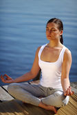 Meisje treinen yoga op de pier in de buurt van lake — Stockfoto