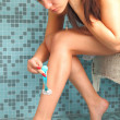 Beautiful girl shaving her legs with razor — Stock Photo #5753420